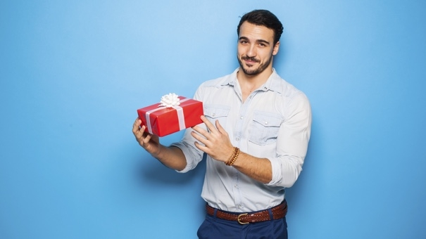 smiling handsome man presenting a red christmas gift, on blue background